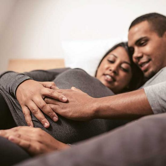 Pregnant couple place hands on belly