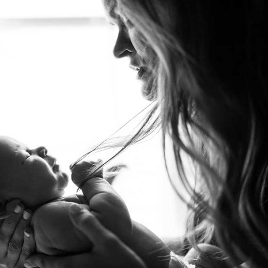 Postpartum mother with newborn baby in black and white photo