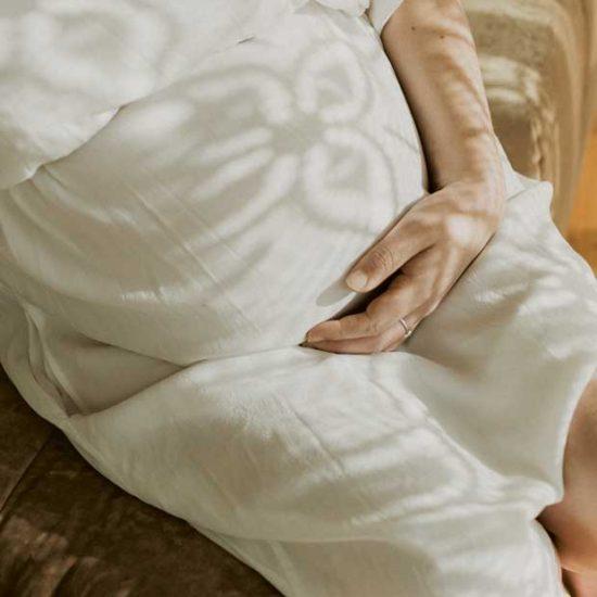 Pregnant mum cradles belly in linen dress