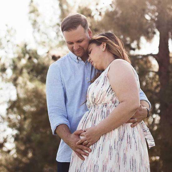 Partner embraces pregnant woman