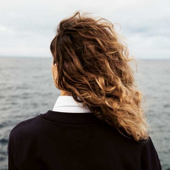 Grieving woman looks out to ocean