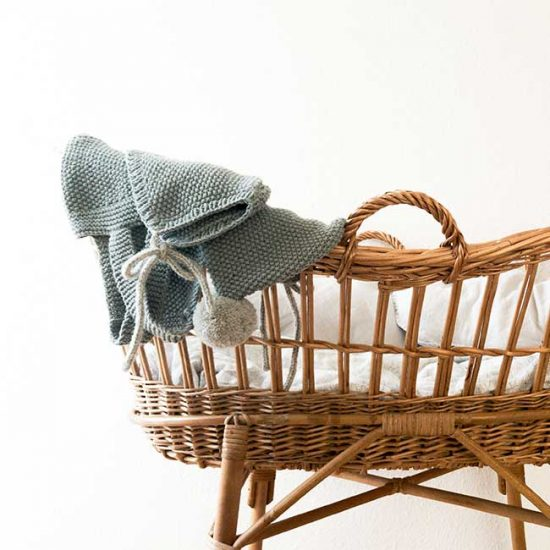 Cane bassinet set up in baby's nursery