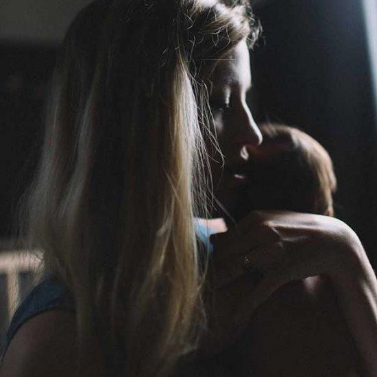 Mum holds newborn baby in dark room