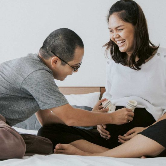 Dad puts baby shoes on mum's pregnant bump