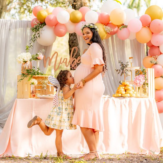 Child kisses mum's pregnant belly at baby shower