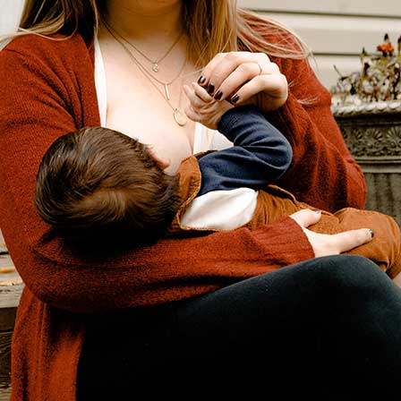 Mum breastfeeds baby in cradle hold position