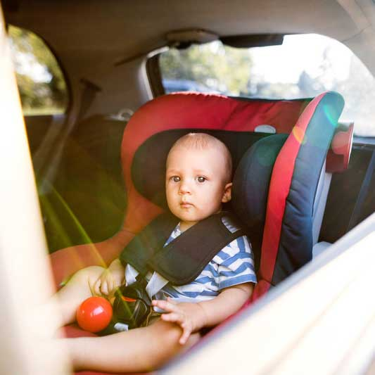 Young baby restrained in car seat