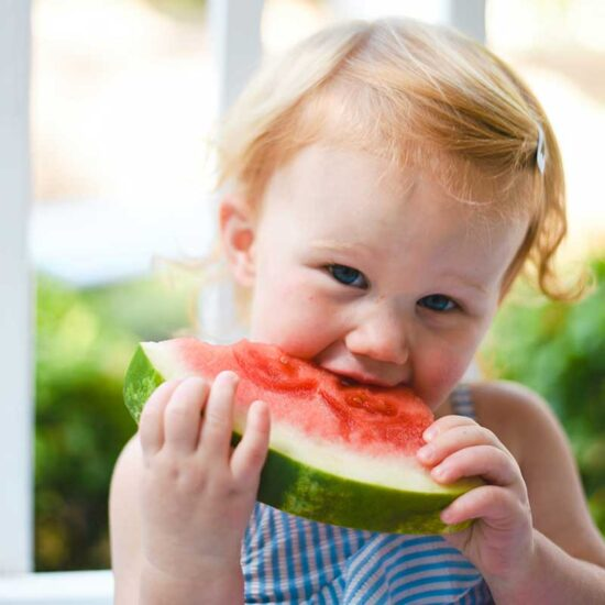 Toddler girl snacking on watermelon