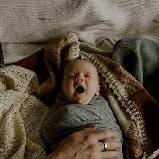 Newborn baby yawns as they fall asleep swaddled