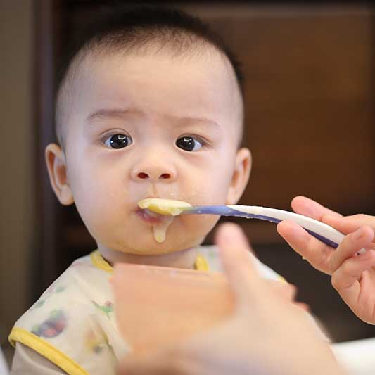 Baby tries traditional spoon-feeding for starting solids