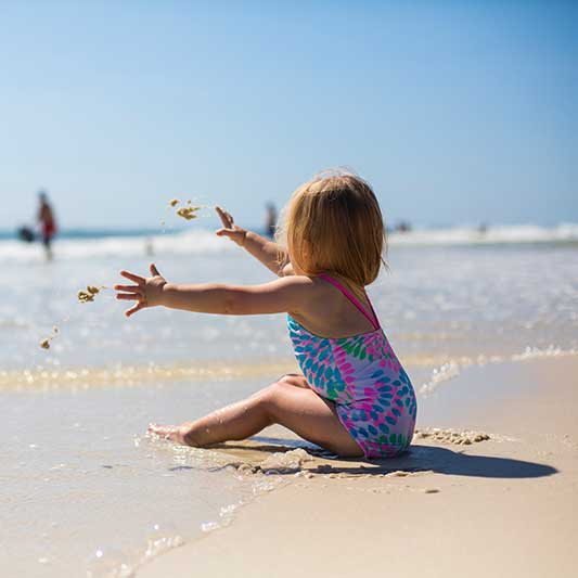 Toddler girl plays with the sand while sitting in the sun at the beach