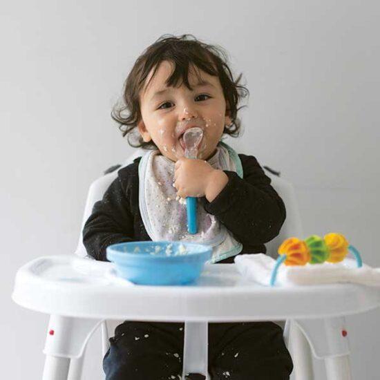 Healthy toddler eating a bowl of porridge