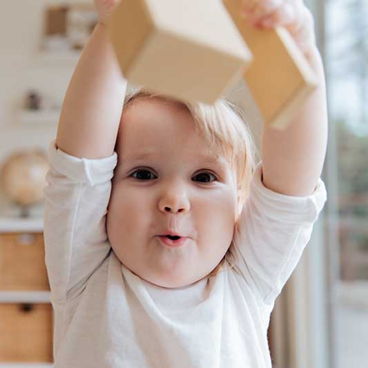 Toddler plays with wooden blocks