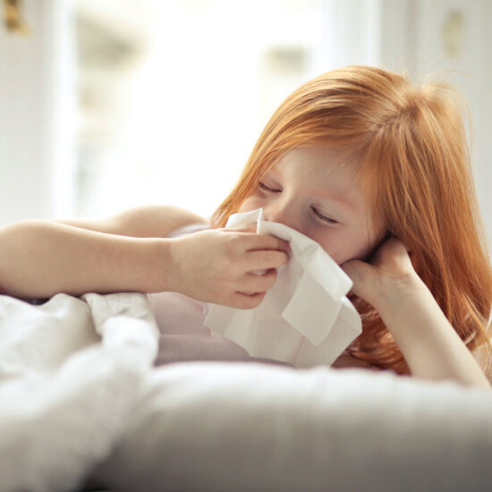 RSV in NZ: Sick child blows her nose with a tissue