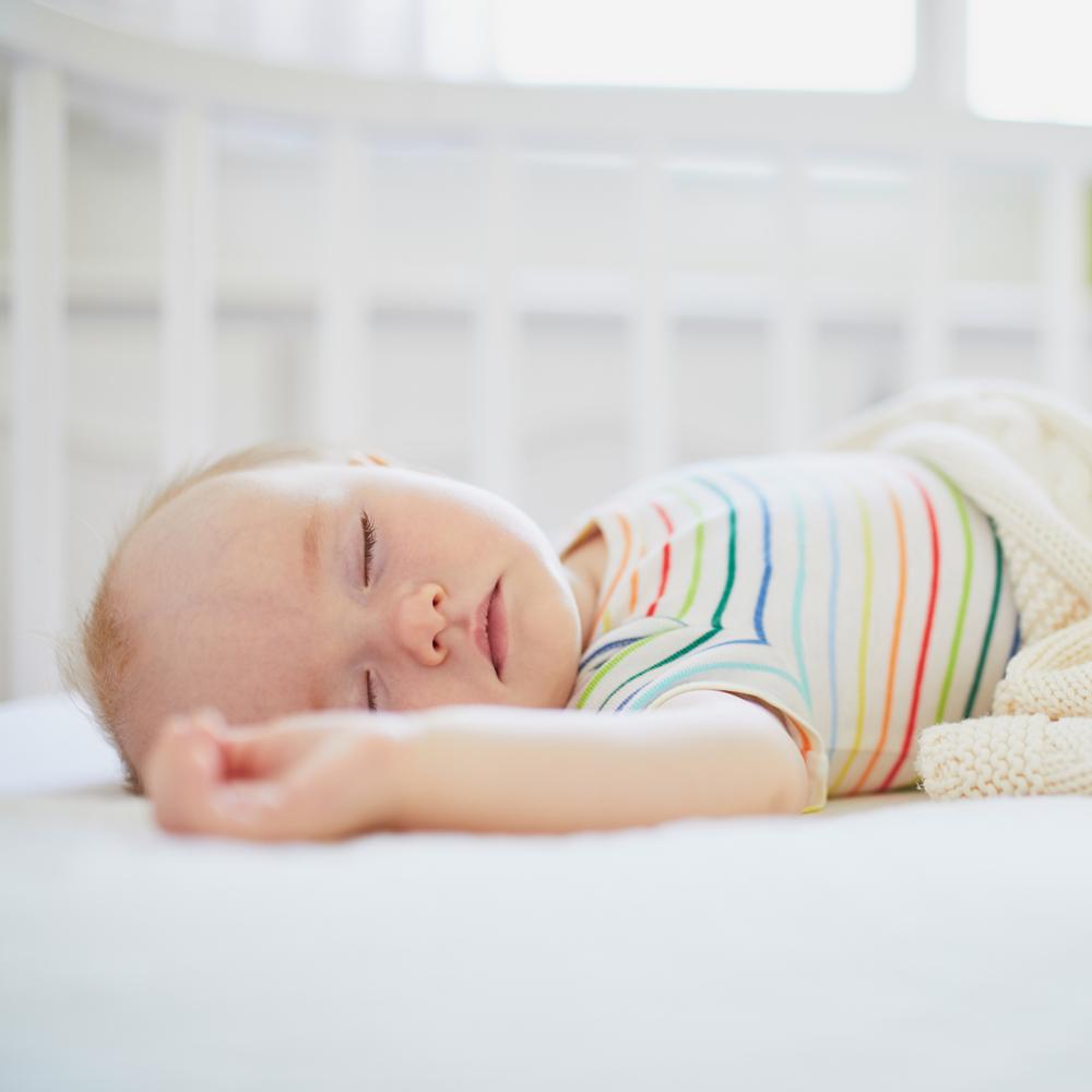 Baby sleeps in cot
